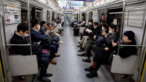 People wearing face masks amid concerns over the spread of Covid-19 commute on a train in Tokyo