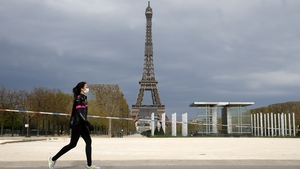 A woman wearing a face mask walks past the Eiffel Tower in Paris, France, today