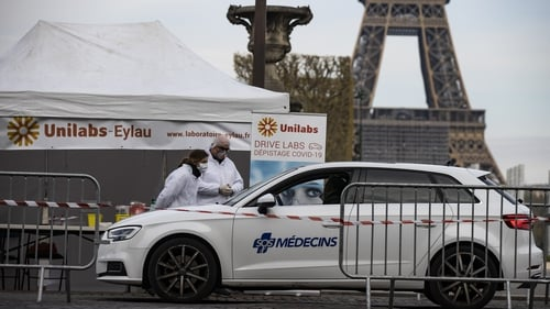 Doctors operate a drive-through coronavirus testing site near the Eiffel Tower in Paris