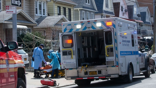 First responders carry a patient on a stretcher from a house in the Queens borough of New York City