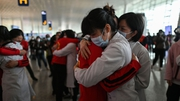 Medical staff from Jilin Province (in red) hug nurses from Wuhan after working together during the coronavirus