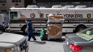 A worker pulls a pallet of disinfectant wipes past a specialised medical bus in the Bronx borough of New York