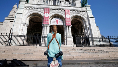 A woman prays in front of Sacre-Coeur Basilica in Paris during a Holy Thursday celebration