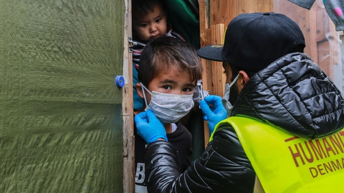 A member of the 'Team Humanity' NGO fits a mask on a child within the Moria camp