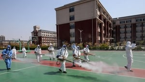 Volunteers spray disinfectant in the compounds of a school in Weifang in China's eastern Shandong province