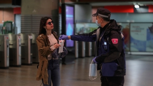 A police officer hands out facemasks at Madrid's Atocha train station