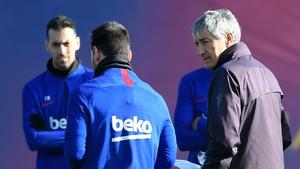 Quique Setien (R), looks at Barcelona captain Lionel Messi besidemidfielder Sergio Busquets (L)