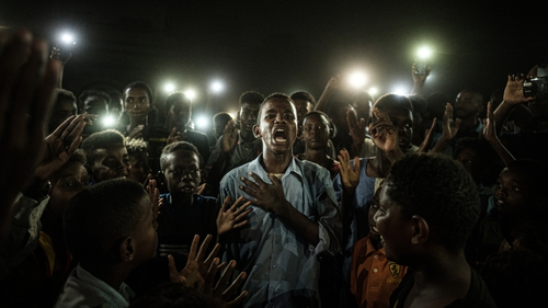 Yasuyoshi Chiba won the prize for his picture of a mobile-lit Sudanese demonstrator reciting protest poetry