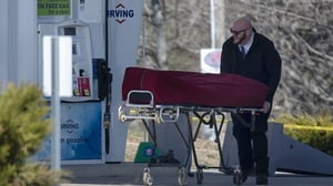 A body is removed following a shooting incident that began in the small coastal village of Portapique, Nova Scotia