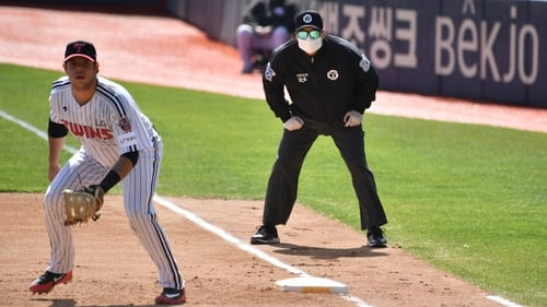 A referee (R) wearing a face mask looks on at first base