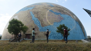 Staff members of the the Gujarat Science City wearing face-masks stand in front of a planet earth model