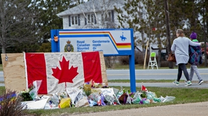 A woman comforts her daughter after they placed flowers at a memorial in Enfield, Nova Scotia