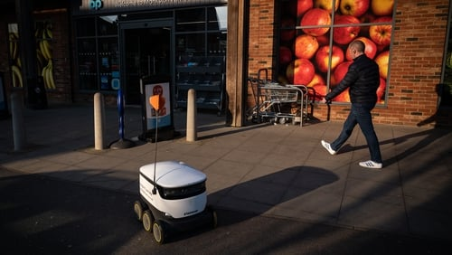 A man walks past a robot as it makes a home delivery in Milton Keynes