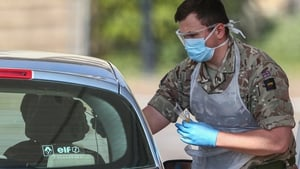 A member of the military takes a swab from a person at a drive-in Covid-19 testing centre at Chessington World of Adventures Resort in England
