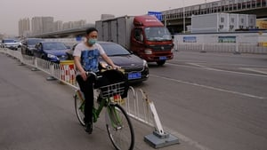 A Chinese cyclist wears a protective mask in Beijing on Friday