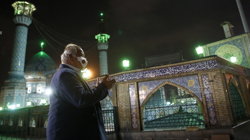 An Iranian man wearing a face mask prays outside the Saleh Shrinein Tehran at the start of Ramadan. Photo: Getty Images