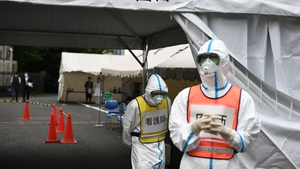 A doctor (R-in orange vest) and a nurse (C-in yellow vest) wearing protective gear in Fujisawa Prefecture, Japan