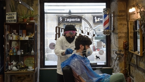 Barber David Cores cuts his first client's hair after reopening his shop in Pontevedra in Spain