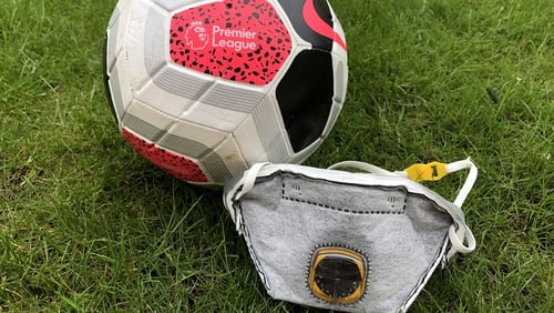 A Premier League Football along side a PPE face mask
