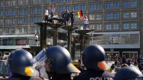 People stood on top of a fountain to protest against the lockdown measures in Berlin