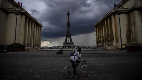 A man rides a bicycle past the Trocadero Esplanade