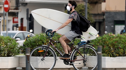 A surfer wearing a protective face mask on his way to the beach in Valencia, Spain