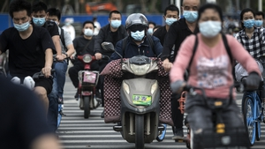Residents wears face masks while riding their motorcycles yesterday in Wuhan