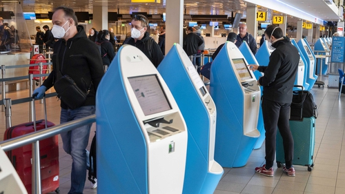 Travellers wearing face coverings at Amsterdam's Schiphol Airport in the Netherlands
