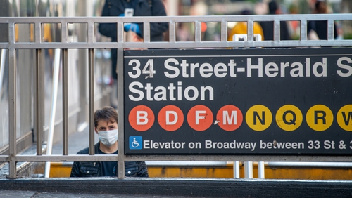A passenger wears a facemask on his way into a subway station in New York city