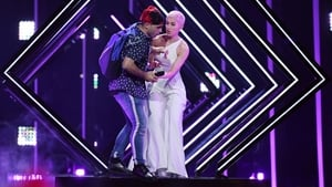 A man takes the microphone from Britain's SuRie as she performs 'Storm during the final in 2018