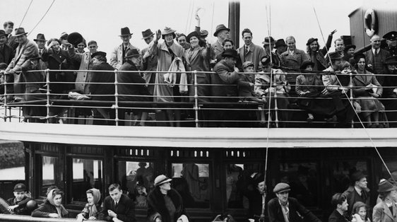Passengers aboard the tender which will transfer them to the 'President Roosevelt' wave farewell to friends on the quayside at Galway harbour. (Photo by © Hulton-Deutsch Collection/CORBIS/Corbis via Getty Images)