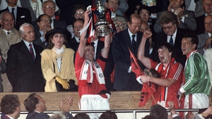 Manchester United captain Bryan Robson holds up the FA Cup in 1990