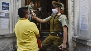 A police officer takes the temperature of a citizen at a police station in Santiago, Chile