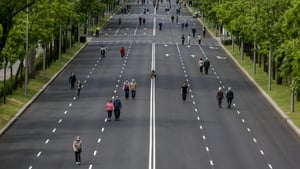 People walk on a deserted road in Madrid