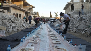 A volunteer prepares a makeshift table for a Ramadan mealamidst the ruins in Atareb town in the western countryside of Syria's Aleppo province. Photo: AAREF WATAD/AFP via Getty Images