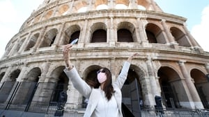 A woman wearing a protective mask takes selfie photos in front of the Colosseum in Rome