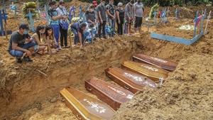 Relatives attend a mass burial in Manaus, Brazil