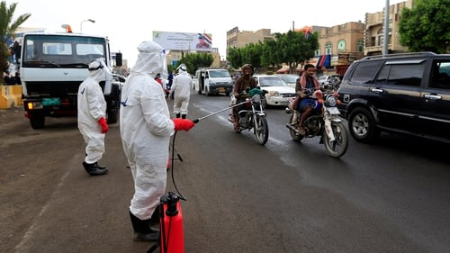 Yemeni workers wearing a protective outfits spray disinfectant on passing cars and motorcycles in Sanaa