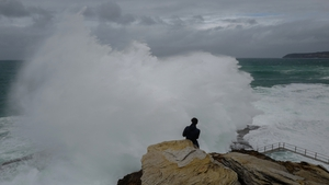 A man photographs stormy conditions at Dee Why Head near Sydney