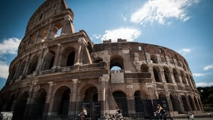 People walk in front of the Colosseum by bicycle in Rome over the weekend