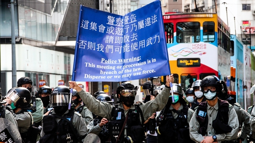 Hong Kong Police raise the blue flag warning protesters, press and pedestrians to disperse during demonstrations in Hong Kong on Sunday