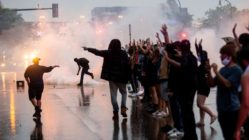 Video showed crowds gathered outside the Minneapolis Police Department's third precinct as riot police fired tear gas
