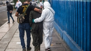 A woman is led away from a hospital in Peru where her husband died of Covid-19