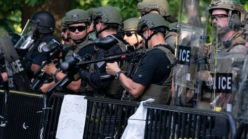 Police officers hold pellet guns during a demonstration in Washington, DC