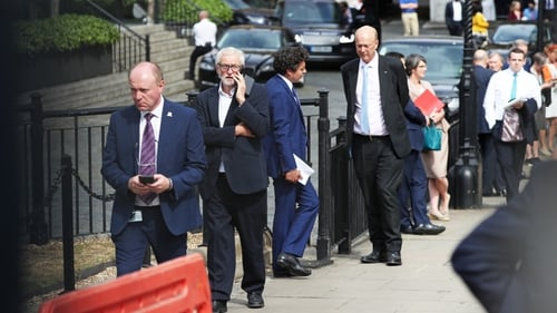 MPs queue outside the House of Commons in Westminster, London, as they wait to vote on the future of proceedings
