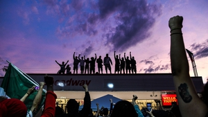 People raise their hands and shout slogans as they protest at a makeshift memorial in Minneapolis