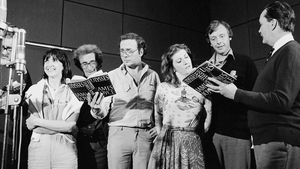 The RTÉ Players record James Joyce's novel 'Ulysses', which was broadcast unedited and uninterrupted by RTÉ Radio 1 (Medium Wave) between 16 and 17 June 1982. The players are standing around the microphone holding their scripts, probably in Studio 1 in RT