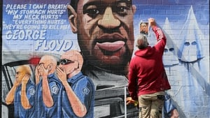 Artist Mickey Docherty removes a photo used to paint a mural of George Floyd in Belfast