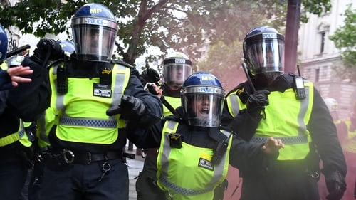 Police officers in riot gear shouting at protesters near Downing Street