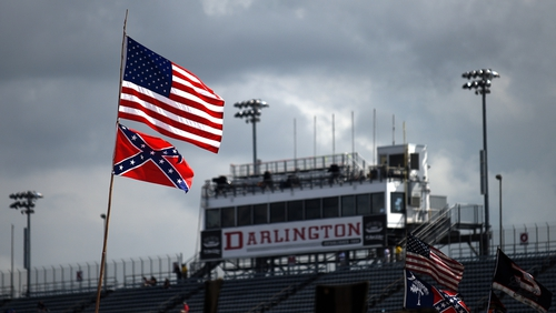The Confederate flag flutters in the breeze beneath the Stars and Stripes at Darlington Raceway in South Carolina in 2015